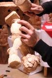 Le mani dell'intagliatore del legno che scolpiscono un angelo di legno in officina Immagine Stock