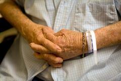 Le mani dell'uomo anziano hanno piegato con il wristband dell'ospedale Fotografia Stock