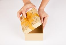 Le mani dell'uomo aprono il contenitore di regalo dorato Immagine Stock Libera da Diritti
