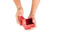 Le mani dell'uomo aprono il coperchio del contenitore di regalo rosso Fotografia Stock Libera da Diritti