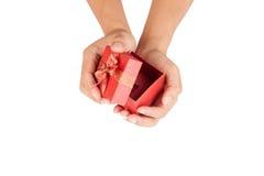 Le mani dell'uomo aprono il coperchio del contenitore di regalo rosso Immagini Stock