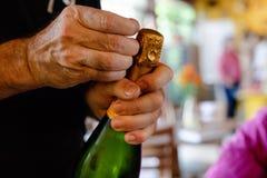 Le mani dell'uomo aprono la bottiglia di champagne immagine stock libera da diritti