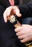 Le mani dell'uomo che aprono una bottiglia di champagne Fotografia Stock
