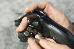 Le mani dell'uomo che caricano le pallottole nella pistola Fotografie Stock Libere da Diritti