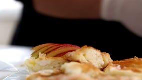Le mani dell'uomo che decorano le torte calde con le mele affettate alla cucina archivi video