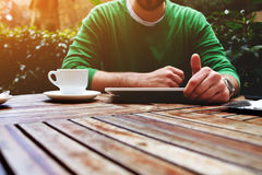 Le mani dell'uomo che mandano un sms al messaggio sulla compressa del touch screen mentre sedendosi sul terrazzo con le piante, c Fotografie Stock Libere da Diritti