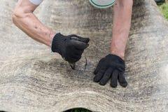 Le mani dell'uomo che tagliano il materiale di tetto Ruberoid Condtruction immagini stock libere da diritti