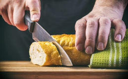 Le mani dell'uomo che tagliano pane sulla plancia di legno Fotografia Stock Libera da Diritti
