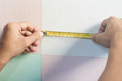 Le mani dell'uomo che tengono misura di nastro Fotografia Stock