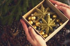 le mani dell'uomo che tengono scatola con le decorazioni di natale dell'oro Progettazione fotografia stock