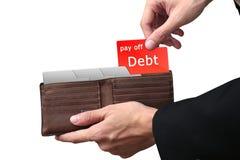 Le mani dell'uomo d'affari che tirano la cartella rossa ripagano il concetto di DEBITO sul bro Immagini Stock