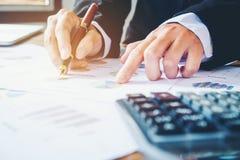 Le mani dell'uomo d'affari con il calcolatore all'ufficio e finanziario Fotografia Stock