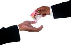 Le mani dell'uomo danno i soldi all'altra mano dell'uomo Immagine Stock