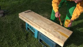 Le mani dell'uomo del carpentiere che dipingono la plancia di legno imbarcano con la spazzola su erba closeup 4K archivi video