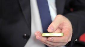 Le mani dell'uomo del primo piano facendo uso dello schermo attivabile al tatto del telefono cellulare stock footage