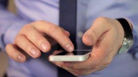 Le mani dell'uomo del primo piano facendo uso dello schermo attivabile al tatto del telefono cellulare video d archivio
