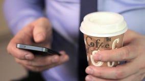 Le mani dell'uomo del primo piano facendo uso dello schermo attivabile al tatto e del cofee del telefono cellulare video d archivio