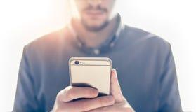Le mani dell'uomo facendo uso dello smartphone fotografia stock