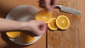 Le mani dell'uomo hanno messo le fette di arancia su un piatto stock footage