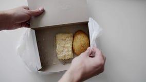 Le mani dell'uomo prende il panino dal contenitore di Libro Bianco disposto nel sacchetto di plastica bianco video d archivio
