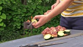 Le mani dell'uomo pugnalano i pezzi dello zucchini e della carne cruda sullo sputo Ustione del fuoco video d archivio
