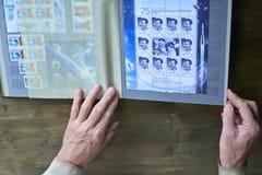 Le mani dell'uomo senior tengono l'album di bollo con la raccolta dei francobolli, Gžatsk ed il tema dello spazio, fondo di legno Fotografia Stock