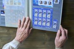 Le mani dell'uomo senior tengono l'album di bollo con la raccolta dei francobolli, il tema dello spazio, fondo di legno Fotografia Stock Libera da Diritti