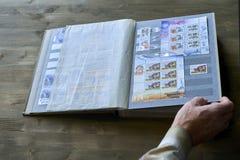 Le mani dell'uomo senior tengono l'album di bollo con la raccolta dei francobolli, il tema dello spazio, fondo di legno Fotografie Stock Libere da Diritti
