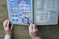 Le mani dell'uomo senior tengono l'album di bollo e della lente con la raccolta dei francobolli, il tema dello spazio, fondo di l Immagine Stock Libera da Diritti