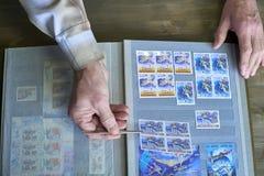 Le mani dell'uomo senior tengono le pinzette e l'album di bollo con la raccolta dei francobolli, il tema dello spazio, fondo di l Immagini Stock Libere da Diritti