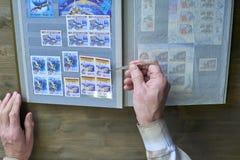Le mani dell'uomo senior tengono le pinzette e l'album di bollo con la raccolta dei francobolli, il tema dello spazio, fondo di l Fotografia Stock