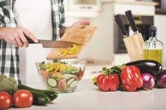 Le mani dell'uomo sta cucinando l'insalata di verdure nella cucina Fotografia Stock
