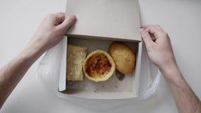 Le mani dell'uomo tengono il sacchetto di plastica bianco con il contenitore di Libro Bianco con il dolce ed i panini video d archivio