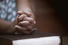 Le mani della bambina hanno piegato nella preghiera su una bibbia santa in chiesa Fotografie Stock Libere da Diritti