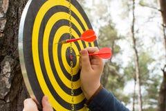 Le mani della bambina hanno rimosso le frecce dal bordo di dardo nel parco Immagine Stock