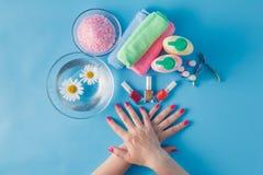 Le mani della bella donna con il manicure perfetto in ciotola di acqua Fotografia Stock