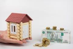 Le mani della casa del giocattolo che stanno i soldi vicini è di comprare l'alloggio Fotografie Stock