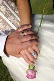 Le mani della coppia con gli anelli e sono aumentato Immagini Stock