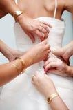 Le mani della donna aiutano la sposa ad abbottonare il vestito da sposa elegante Fotografie Stock Libere da Diritti