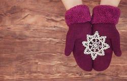 Le mani della donna in alzavola leggera hanno tricottato i guanti stanno tenendo il giocattolo di Natale su fondo di legno Invern immagini stock libere da diritti