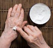 Le mani della donna anziana che applicano crema Fotografia Stock
