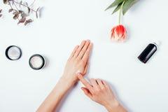 Le mani della donna applicano la crema su pelle per provarla Vista superiore Fotografie Stock