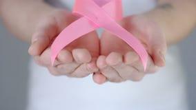 Le mani della donna che danno il nastro rosa di consapevolezza del cancro al seno - concetto di consapevolezza del cancro al seno video d archivio