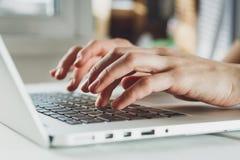 Le mani della donna che lavorano al computer portatile Fotografia Stock