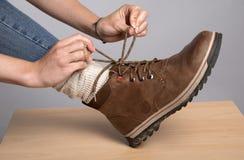 Le mani della donna che legano un arco sui suoi stivali di camminata Fotografia Stock