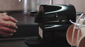 Le mani della donna che producono caffè fresco che esce da una macchina di caffè espresso del caffè Produrre caffè espresso in ta archivi video