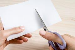Le mani della donna che tagliano carta con le forbici Fotografie Stock Libere da Diritti