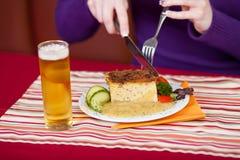 Le mani della donna che tagliano pasto delizioso con la forcella e coltello a Tabl Fotografie Stock Libere da Diritti