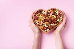 Le mani della donna che tengono il cuore hanno modellato la ciotola con i dadi misti sulla vista rosa del piano d'appoggio Alimen fotografia stock libera da diritti