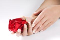 Le mani della donna con colore rosso sono aumentato fotografia stock